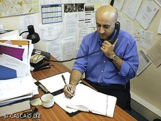 A man is sitting at a desk, using a telephone.  He is writing on a notepad.
