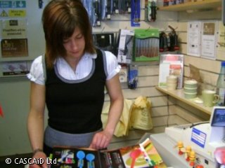 A woman stands behind the counter in a shop.  She is looking through a catalogue with photos of brightly coloured cookware.
