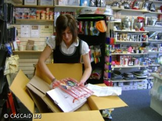 A woman stands in a shop, unpacking items from a large cardboard box.