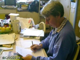 A woman is sitting at a kitchen table, checking something on a paper form.  There are booklets and paperwork on the table.