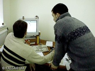 A man is sitting at a desk, using a computer.  Another man is standing beside him.  They are both looking at the computer screen and talking to each other.