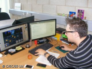 A man wearing a striped jumper and glasses is sitting at a desk, using a computer.  There are two large monitors on the desk.  On one of the monitor screens, there is a colourful game.
