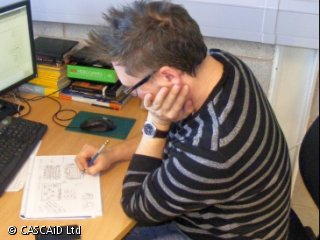 A man wearing a striped jumper and glasses is sitting at a desk.  He is drawing in pencil on an A4-sized pad of paper.