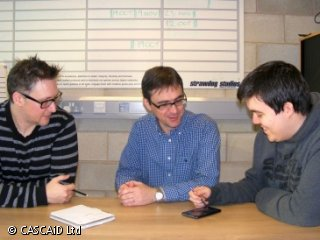 Three men are sitting at a table in an office.  One of the men has a smart phone and the other two are looking at something on the phone.  There is a large whiteboard planner on the wall behind them.