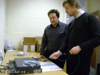 Two men are standing by a desk in an office.  On the desk there is some computer equipment, along with various cables and boxes.  One of the men is holding a computer cable.
