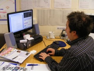 A man wearing a striped shirt is sitting at a desk, typing on a computer keyboard and looking at the screen.  There are various paper charts and lists on the wall behind the desk.
