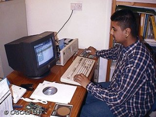 A man is sitting at a desk, using a computer.  The computer cover has been taken off.  There are some CDs on the desk.