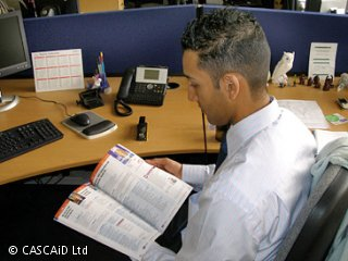 A man sits at an office desk, reading a computer magazine.