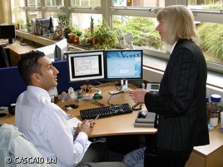 A man is sitting at a desk near a window.  There are two computer monitors on the desk.  A woman is standing next to him and they are talking.