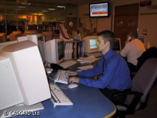 A man is sitting at a long desk full of computer screens.  He is using a computer.  Another man sits next to him, using a telephone and a computer.  There is a large monitor screen high up on the wall.