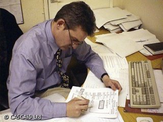 A man sits at a desk which has many paper documents on it.  He is studying one of documents, which has a series of diagrams on it.