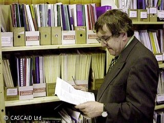 A man, wearing a suit and tie, is standing by a row of shelves full of various booklets and pamphlets.  He is reading a paper document.