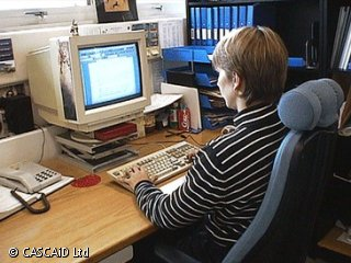 A woman is sitting at a desk, using a computer.  There is a row of blue folders on a shelf next to the desk.