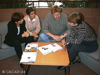 Four people are sitting on a sofa, talking.  There is a small wooden table in front of them.  They are consulting some brochures, which are lying on the table.