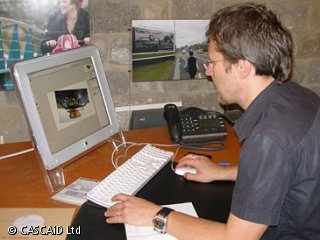 A man is sitting at a desk, using a computer.