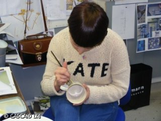 A woman wearing a jumper with her name on it is painting a pattern on to a white cup.