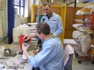 Two men are in a workshop.  They are both wearing blue lab coats. One man is standing.  The seated man is working on a piece of clay.
