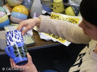 A woman is comparing two patterned mugs.