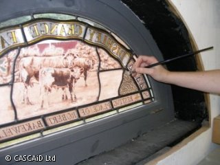 A woman is painting a semi-circular section of stained glass.