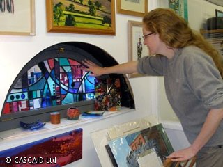A woman is inspecting some stained glass.  There are some pictures in frames on the wall above it.