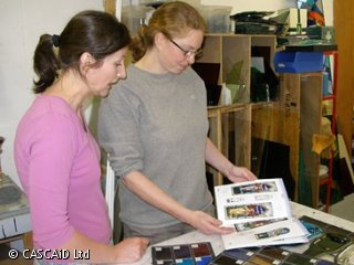 Two women are standing in a design studio.  They are looking at some colourful images.