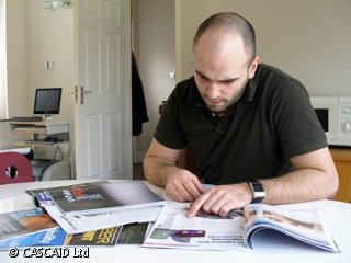 A man is sitting at a desk, looking through some magazines.