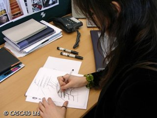 A woman is sitting at a desk, drawing on a piece of paper.