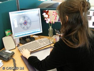 A woman is sitting at a desk, using a computer.  She is using design software.