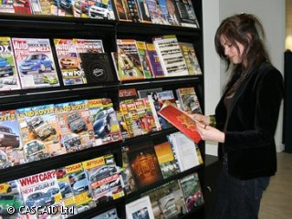 A woman is standing, reading a magazine.  There are many magazines on the shelves behind her.