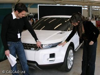 A man and a woman are inspecting a white car.
