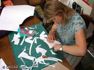 A woman is sitting at a table, cutting out patterns from a large sheet of white paper.