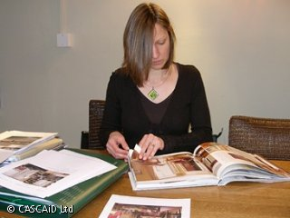 A woman is sitting at a table looking through a large brochure.  There are folders on the table and other paper documents.