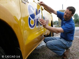 A man is crouching down and attaching a sign to the side of a yellow car.  He is outside.