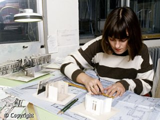 A woman is sitting at a desk.  In front of her is a large sheet of white paper.  She is using a ruler to measure a diagram on the paper.  There are also some small white models and two pencils on the desk.
