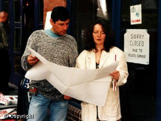 A woman and a man are both looking at a large sheet of white paper.  They are stood next to a door with a sign on it saying: 'Sorry closed due to flood damage.'