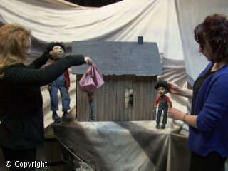 Two women are holding puppets in front of a theatre set.