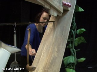A woman, wearing a blue cardigan, is working on a wooden theatre set.