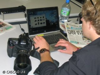 A man is working on a laptop computer.  Next to him is a newspaper and a large camera.
