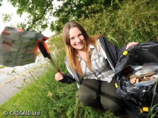 A girl is outdoors. She is holding a piece of litter in some tongs and has a black bin bag next to her.