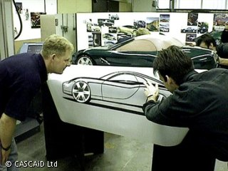 Two men are bending down and carefully examining a picture of a car, drawn on a large sheet of paper.  Behind the sheet of paper there is an actual model of a car.