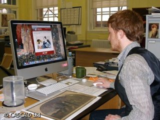 A man is sitting at a desk, using a computer.  He is using the internet to search for photos.