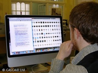 A man is sitting at a desk, using a computer.  On the screen there are many small images and some text.