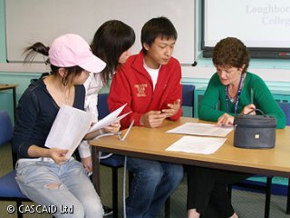 A woman is sitting at a table, looking at a piece of paper.  Three students are also sitting at the table, looking at the paper.