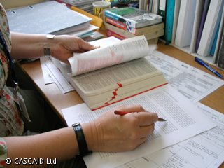 A woman is flicking through a book while marking a document.