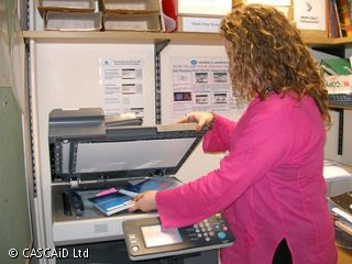 A woman is placing a book onto the glass plate of a photocopier.