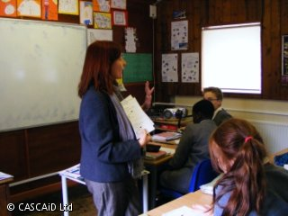 A female teacher is standing in front of the class. She is showing the students a worksheet.