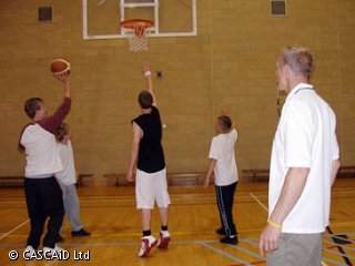 A man is standing in a gymnasium, watching four students playing basketball.  He has a whistle in his mouth.