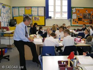 A man is sitting on a desk, at the front of a classroom.  Children are sitting at desks and listening to the man.