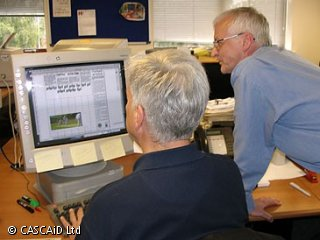 A man is sitting at a desk in an office.  He is using a computer.  Another man is standing next to him, also looking at the computer.