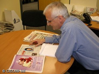 A man is sitting at a round table, reading a magazine.  There is a notepad in front of him.
